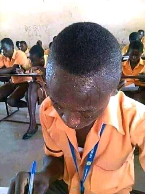 A boy writing exam and sweating